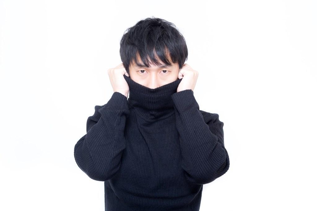 寒さに震えタートルネックで首元を隠す男性