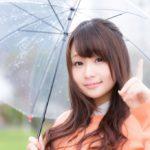 雨が降って傘を差している女性