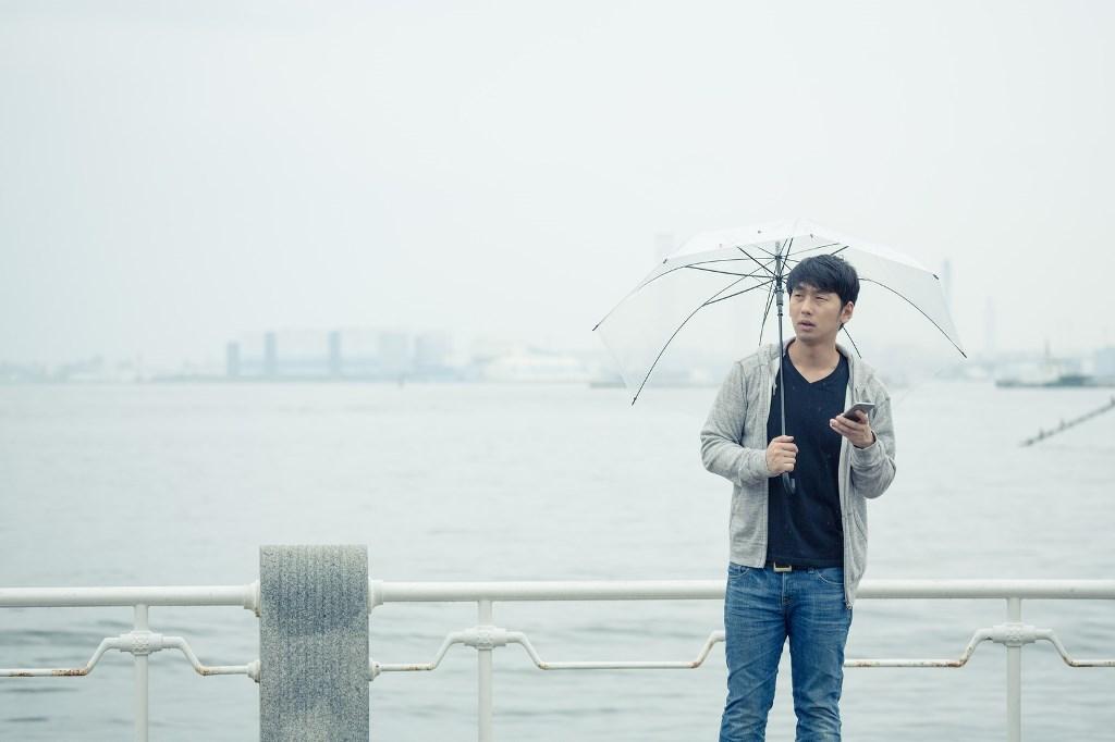 雨の中で友人を待つ男性