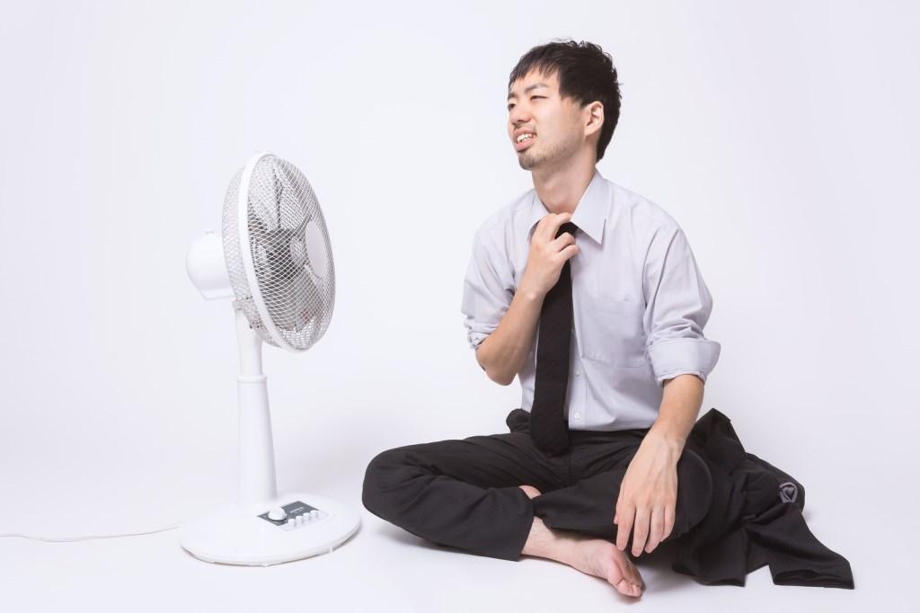 扇風機にあたる男性